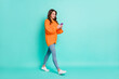 Full size profile side photo of young beautiful positive smiling girl go walk using smartphone isolated on teal color background