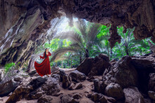 Asian Female Traveler In Red Dress Visit Hup Pa Tat Cave In Uthai Thani Province, Thailand