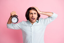 Photo Of Stressed Funny Guy Hold Clock Oversleep Wear Spectacles Blue Shirt Isolated On Pink Color Background