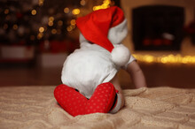Cute Little Baby Wearing Santa Hat On Blanket At Home, Back View. Christmas Celebration