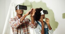 Close Up Of African American Couple With Impressed Excited Faces Stand In Room During Renovation In VR Glasses And Looking At New Redesigned Renewed Apartment Using Virtual Reality Technology