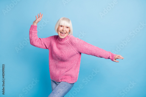 Photo portrait of cheerful old woman dancing isolated on pastel blue colored background