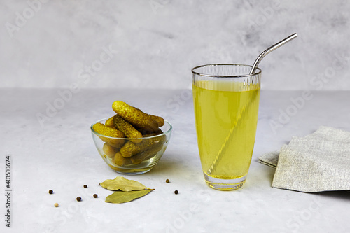 Obraz na płótnie Cucumber pickle or pickle juice in glass with a metal tube for drinks , a bowl with pickled gherkins on light background