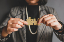 Cropped Shot Of Business Woman Connects Puzzle Piece With Blurry On The Background. Free Time At Work, Selective Focus, Blurred