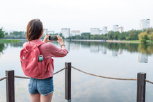Woman In Summer In City Near Lake, River Pond, Photographing Landscape Smartphone, Recording Video On Internet, Application Smartphone Camera. Background Water Pier Jetty. Free Space For Copy Of Text.
