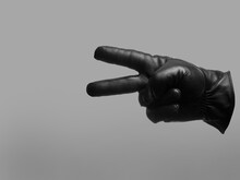 Black Leather Glove Shows Two Fingers Gesture. Isolated Neutral Background. Copy Space