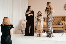 Girl Photographer Takes Pictures Of Three Beautiful Girls In Long Dresses Against The Backdrop Of A Horse Sofa In The Studio. Towards A Fashion Style. Little Girl With Kukkkola In Hand. Family Photo.