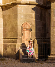 Portraits Of A Beautiful Young Woman In The Hard Light Of The Sun. A Girl In Dress And Straw Hat Sits On A Staircase Near The Black Church In Brasov Romania. Girl And Wooden Door Into Fairy Wonderland