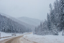 Snow-covered Highway Among The Mountains, On The Sides There Are Trees And Trees In The Snow. Winter Landscape With Snow-covered Road, Fir Trees And Mountains In Montana, America, 1-18-2020