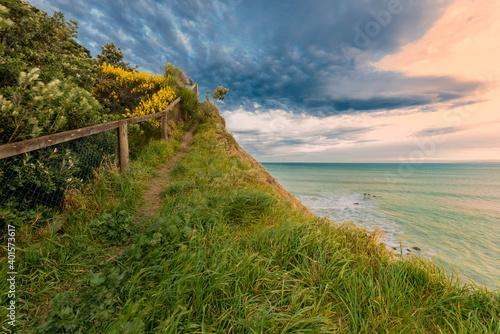Fotomural Grassy hillside at sunset under a colorful sky
