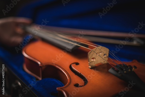 Photo Musician delicately takes out his instrument from its blue case, the wood-colored violin in his hand is accommodated