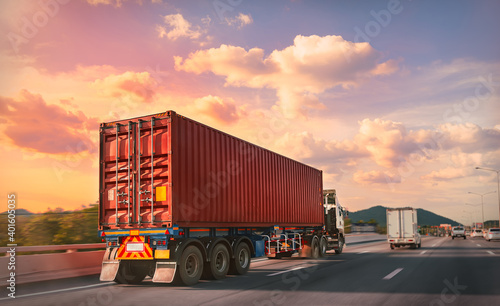 Truck with red container on the highway with sunset time, logistic import export and transport industry concept