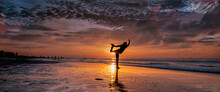 Panorama Of A Silhouette Of A Woman Practicing Yoga On The Beach During A Beautiful Sunset. Long Cover Or Social Media