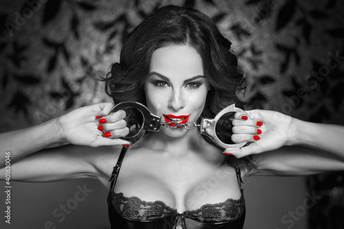 Sexy woman holding handcuffs in nightclub black and white selective coloring