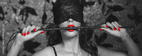 Fototapeta Sexy woman in blindfold bite whip black and white selective colored banner