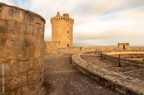 Fotografie, Obraz Tower of Bellver castle with clouds in motion in the sky in Mallorca, Spain