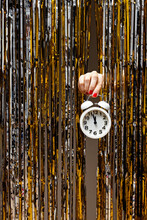 Feminine Hand Holds Clock Showing Almost Midnight
