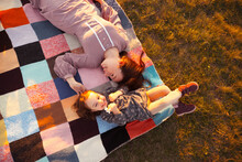 From Above Delighted Young Woman Touching Cheerful Girl With Flower While Relaxing On Checkered Coverlet In Weekend In Meadow