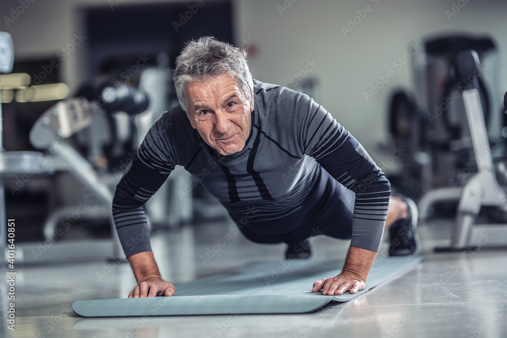 Fototapeta Age is just a number to a man with grey hair doing pushups in a gym