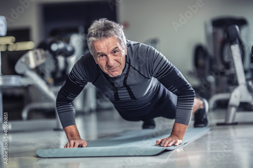 Obraz Age is just a number to a man with grey hair doing pushups in a gym - fototapety do salonu