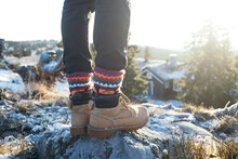 Male Legs In Black Pants And Hand Knitted Wool Traditional Ornament Socks, Leather Suede Winter Boots Or Hiking Shoes. Man On Cold Frosty Mountain Walk In Snow In Scandinavia