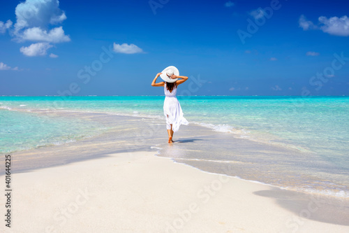 Obraz A woman in a white summer dress stands on a sandbar surrounded by turquoise ocean in the Maldives islands - fototapety do salonu