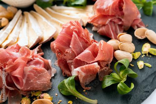 Fototapeta Tagliere con prosciutto crudo, brie, confettura di frutta, pistacchi e noci, antipasto italiano obraz