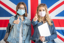 Two Teenage Female Students Wearing Protective Masks Show Thumbs Up Standing In Front Of The UK Flag