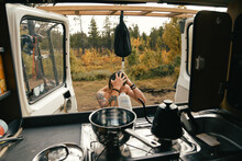 View From Inside Camper Van On Young Hipster Man Take Shower Outdoors From Camping Pocket Shower. Life Inside Converted Camping Van On The Road. Vanlife Lifestyle Concept. Funny Camping