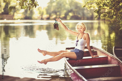 Obraz Carefree young blonde woman enjoying the sunny summer day on a vintage wooden boats on a lake in pure natural environment on the countryside. - fototapety do salonu