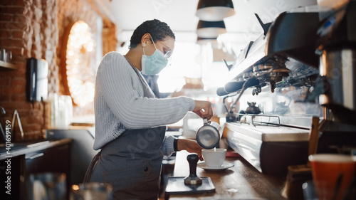 Papel de parede Beautiful Latin American Female Barista in Face Mask is Making a Cup of Cappuccino in Coffee Shop Bar