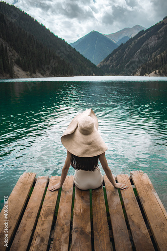 Obraz A girl in a hat sits on the pier and looks at the Kolsai lake - fototapety do salonu