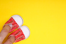 Male Hand With Baby Shoes In Red With White Polka Dots On A Yellow Background