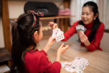 自宅でカードゲームをする母と娘