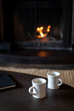 Two Mugs Of Coffee On A Table In Front Of Wood Burning Fireplace