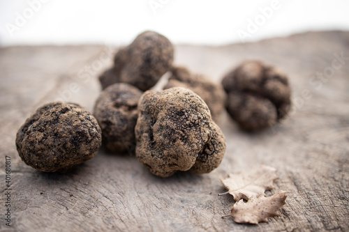 Black truffles on a wood surface.