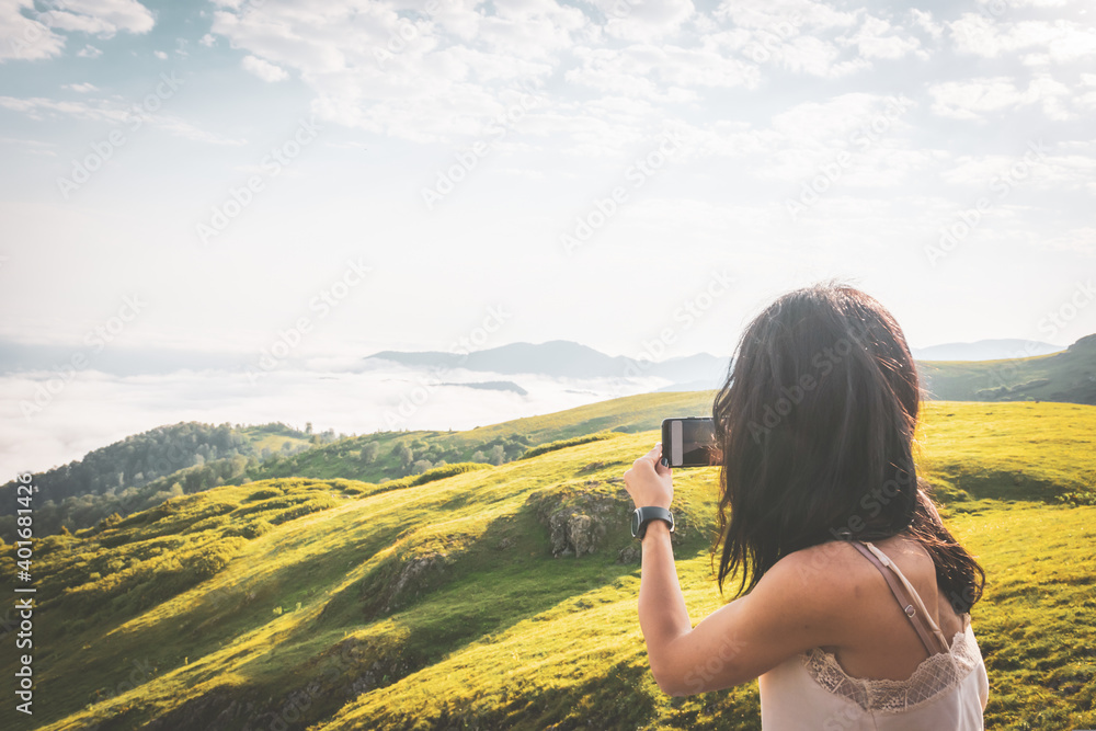 Fototapeta Close up back view of brunette woman taking smartphone photo of scenic dreamy meadow views