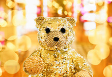 Gold Teddy Bear On Shiny Gold Bokeh Abstract Background