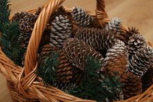 Rustic Handmade Basket With Pine Cones On Wooden Background
