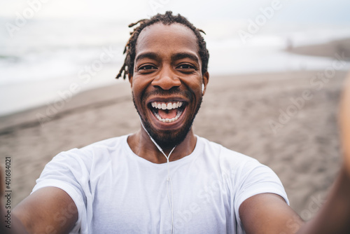 Fotomural Laughing black man holding camera and taking selfie on seacoast