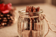 Cinnamon Sticks And Cubes Of Brown Sugar In Glass Jar And Table Decoration On Brown Background. Close Up. Horizontal