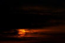 A Rising Sun Shows Through Dark Clouds.