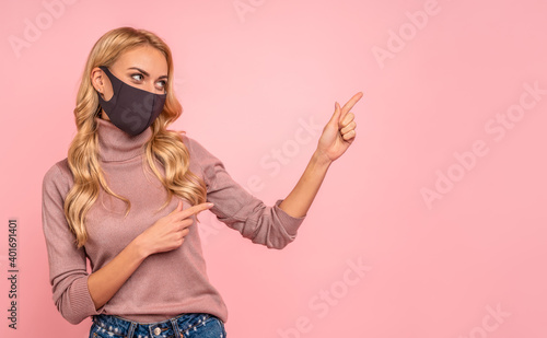 Foto Young woman in pink blouse, sterile face mask to safe from coronavirus virus covid-19 during pandemic quarantine pointing fingers on workspace mock ups copy space isolated on pastel pink background