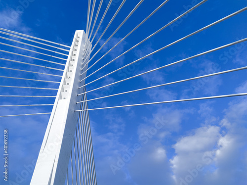 Fototapeta premium Pylon and cables of a cable-stayed bridge - white lines and concrete pillar against blue sky with clouds, on a sunny day. Millennium bridge in Podgorica, Montenegro.