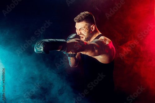 Fotografie, Obraz Bearded tattooed sportsman muay thai boxer in black undershirt and boxing gloves fighting on dark background with smoke