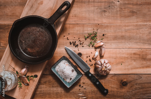 Iron pan, on a kitchen table, accompanied by seasonings, salt with spices, kitchen knife, garlic, and fresh oregano on a rustic madara background