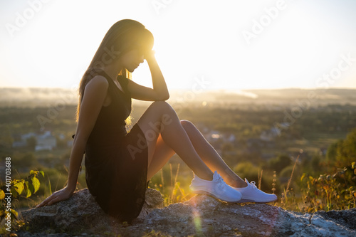 Obraz Young elegant woman in black short dress and white sneaker shoes sitting on a rock relaxing outdoors at summer evening. Fashionable lady enjoying warm sunset in nature. - fototapety do salonu