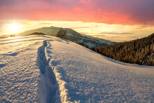 Human Footprint Track Path In White Deep Snow Through Empty Field With Woody Dark Mountain Range And Soft Glow On Horizon At Sunset.