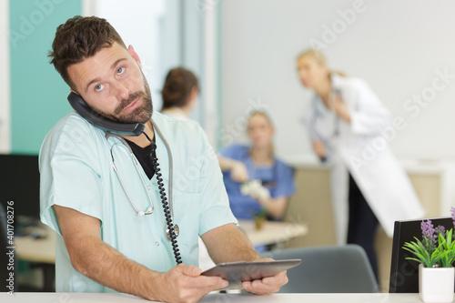 Obraz doctor on the phone holding the tablet - fototapety do salonu
