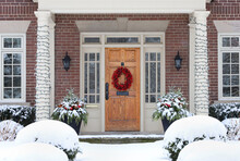 Wood Grain Front Door Of House With Colorful Christmas Wreath With Snow Covered Shrubs